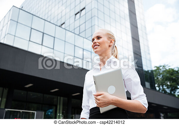 Businesswoman holding digital tablet while looking away against office building - csp42214012