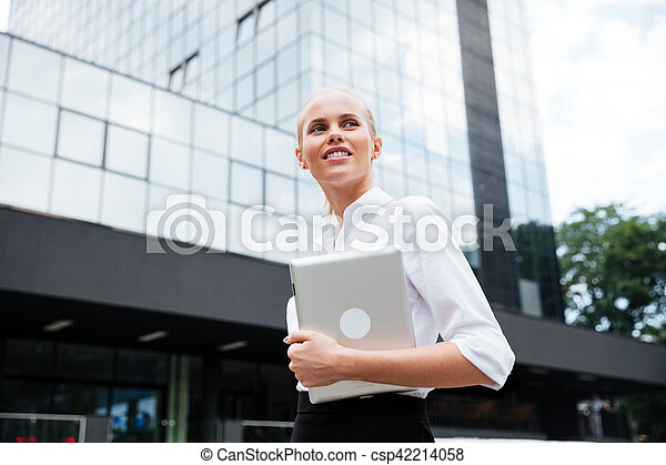 Businesswoman holding digital tablet while looking away against office building - csp42214058
