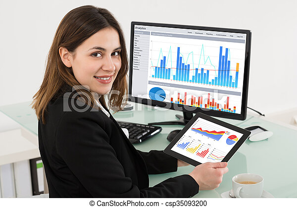 Businesswoman Holding Digital Tablet While Working In Office - csp35093200