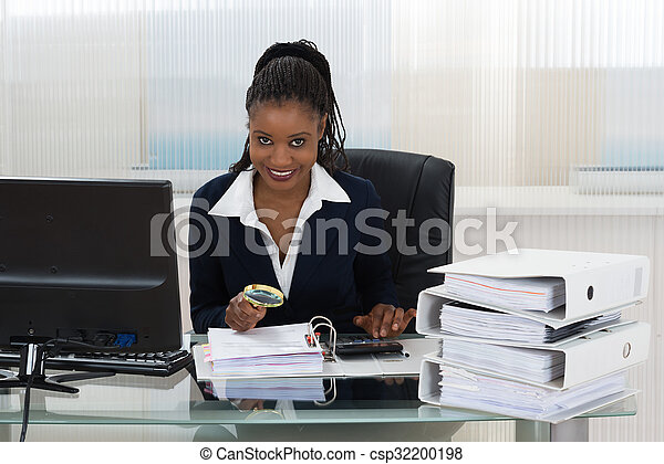 Businesswoman Holding Magnifying Glass Over Invoice - csp32200198