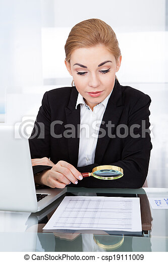 Businesswoman Holding Magnifying Glass - csp19111009