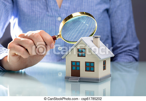 Businesswoman Holding Magnifying Glass Over House Model - csp61785202