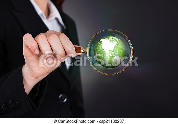 Businesswoman Holding Magnifying Glass Over Globe - csp21188237