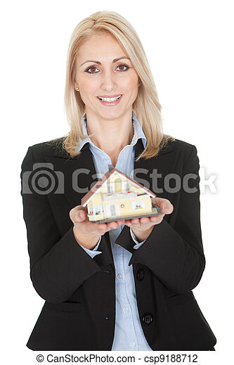 Businesswoman holding model of a house - csp9188712