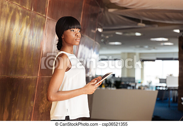 Businesswoman holding tablet computer in office - csp36521355