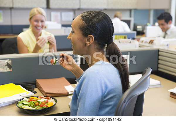Businesswoman in cubicle eating salad and smiling - csp1891142