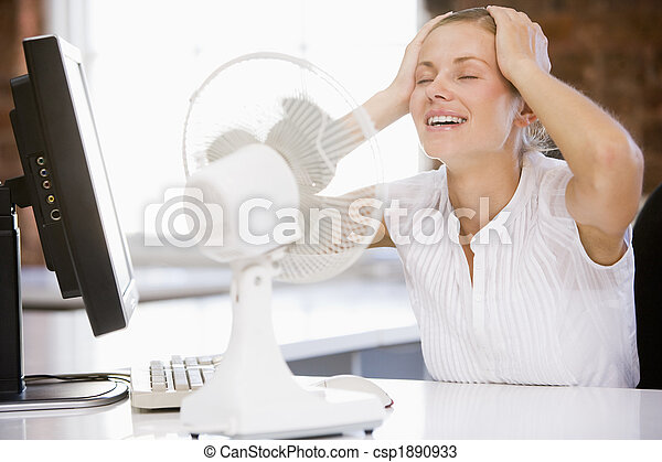 Businesswoman in office with computer and fan cooling off - csp1890933
