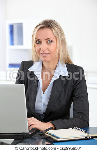 Businesswoman in the office with laptop computer - csp9959501