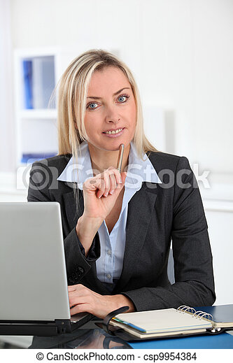Businesswoman in the office with laptop computer - csp9954384