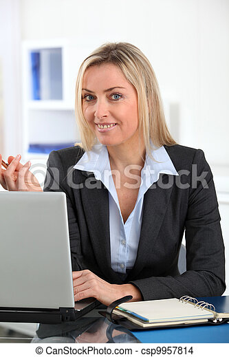 Businesswoman in the office with laptop computer - csp9957814