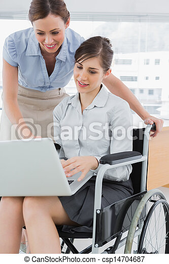 Businesswoman looking at co workers laptop who is sitting in wheelchair in the office - csp14704687