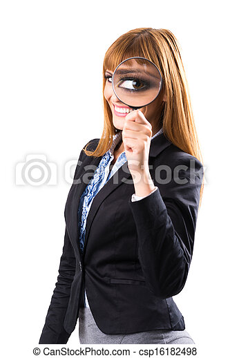 Businesswoman looking through magnifying glass - csp16182498