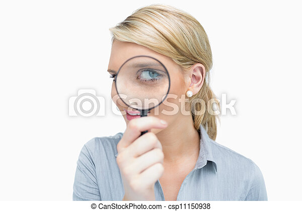 Businesswoman looking through magnifying glass - csp11150938