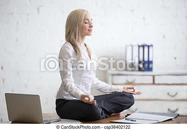 Businesswoman Meditating In Her Office   Csp36402122