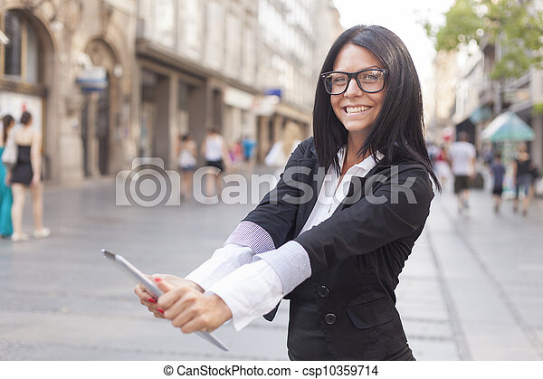 Businesswoman on street holding tablet computer - csp10359714