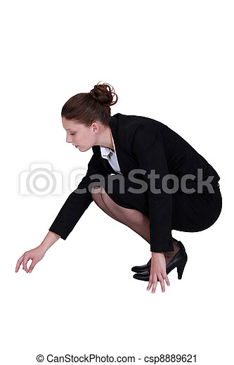 Businesswoman picking a speck up off the floor - csp8889621