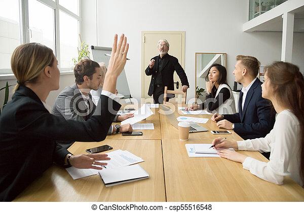 Businesswoman raising hand asking senior coach questions at team - csp55516548