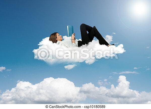 Businesswoman reading a book in a cloud - csp10180589