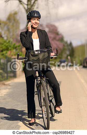 Businesswoman riding to work pausing for a call - csp26989427