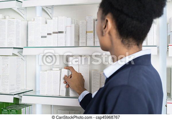 Businesswoman Selecting Medicine In Pharmacy - csp45968767