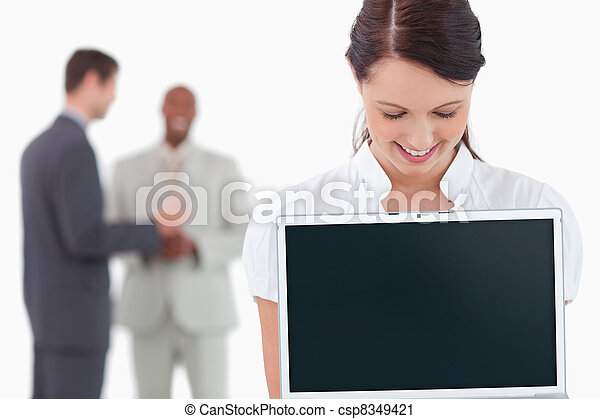 Businesswoman showing laptop with associates behind her - csp8349421