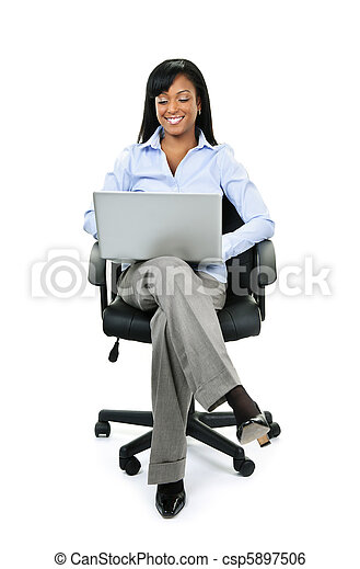 Businesswoman sitting in office chair with computer - csp5897506