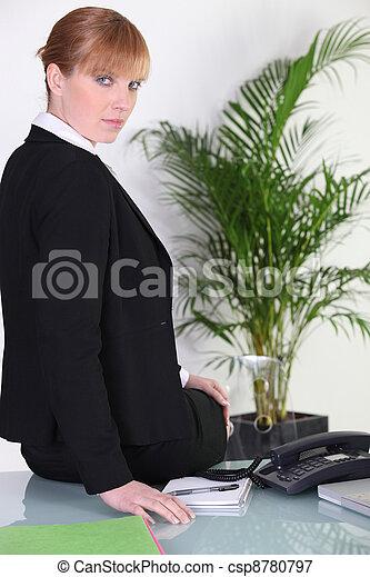 Businesswoman sitting on her desk - csp8780797