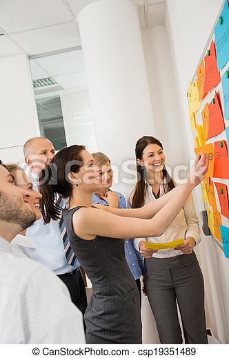 Businesswoman Sticking Labels On Whiteboard - csp19351489