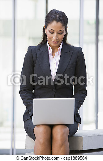 Businesswoman using laptop computer outside - csp1889564