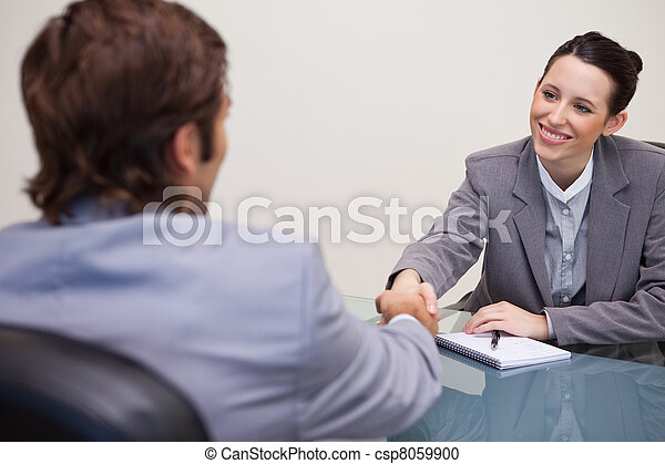 Businesswoman welcomes customer in her office - csp8059900