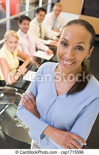 Businesswoman with four businesspeople at boardroom table in background - csp1715596