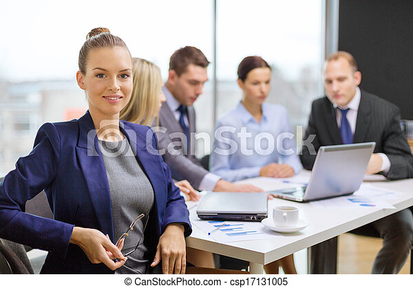 businesswoman with glasses with team on the back - csp17131005