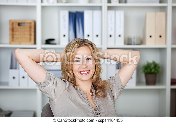 Businesswoman With Hands Behind Head In Office - csp14184455