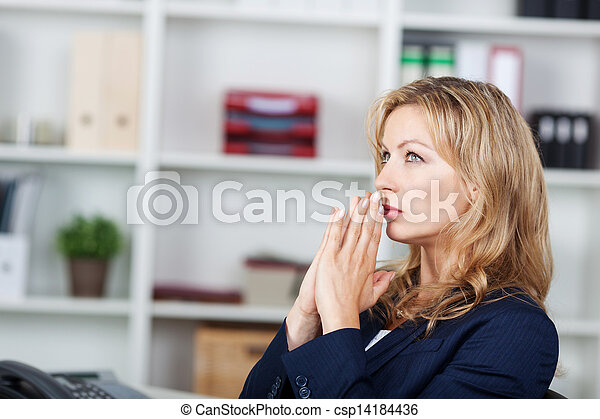 Businesswoman With Hands Clasped Looking Away In Office - csp14184436