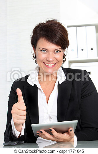 Businesswoman with tablet giving thumbs up - csp11771045
