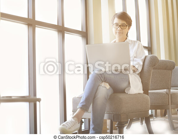 Businesswoman working in office with laptop computer - csp50216716