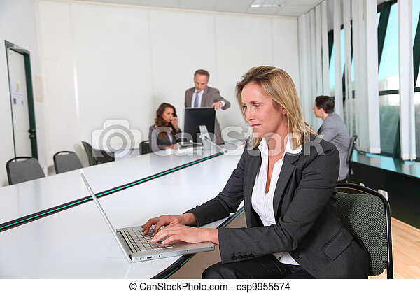 Businesswoman working in office with laptop computer - csp9955574
