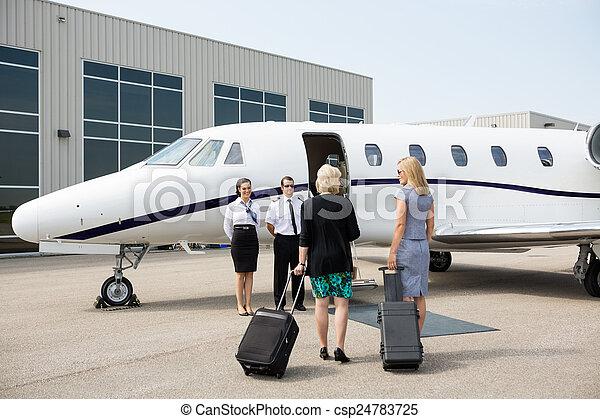 Businesswomen Walking Towards Private Jet - csp24783725