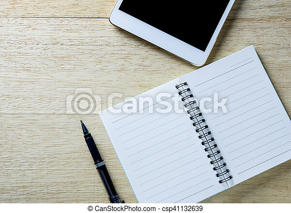 Busy desk of a businessman with an open diary and tablet. - csp41132639
