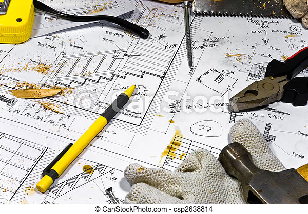Busy hobby workbench. Different carpenter tools: saw, hummer, tape measure, pliers are lying in the saw dust upon the blueprints and drawings along with screws, pencil and protective gloves. - csp2638814