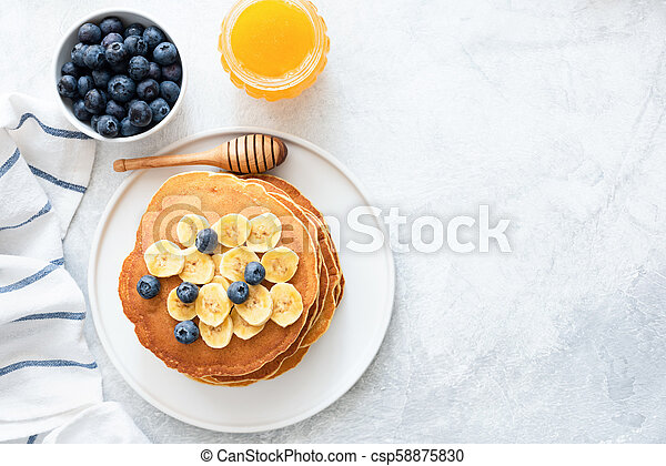 Buttermilk Pancakes with banana, blueberries and honey on concrete background - csp58875830