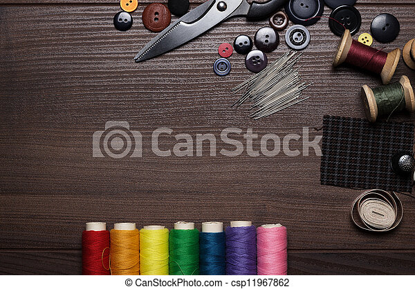buttons, needles and multicolored threads on wooden table - csp11967862