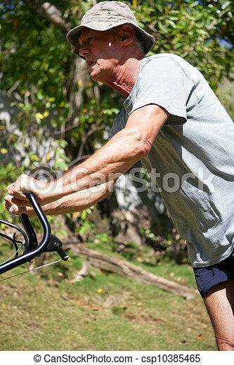 Un veterano moviendo el césped - csp10385465