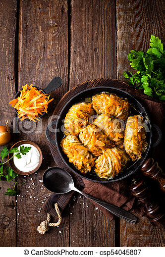 Cabbage rolls stewed with meat and vegetables in pan on dark wooden background, top view - csp54045807