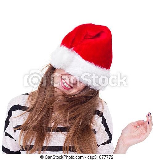 Una chica con un sombrero de Navidad rojo agita su cabeza - csp31077772