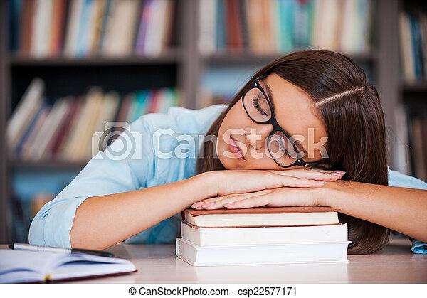 Exam agotamiento. Mujeres jóvenes cansadas sosteniendo su cabeza en la estantería de libros y durmiendo mientras están sentados en el escritorio de la biblioteca - csp22577171