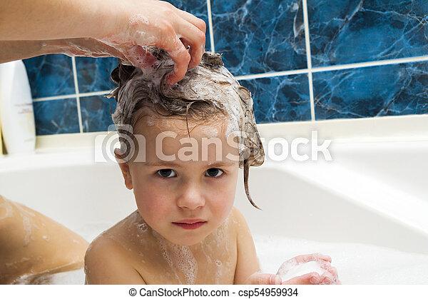 Las manos de mamá lavando la cabeza de la niña en el baño. El símbolo de la pureza y la educación de la higiene. - csp54959934