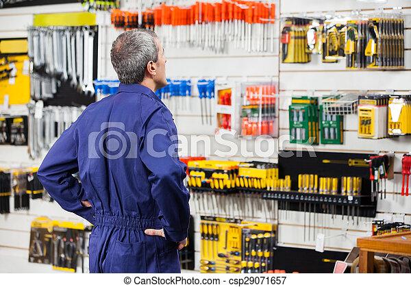 Trabajador con las manos en la cadera en la ferretería - csp29071657