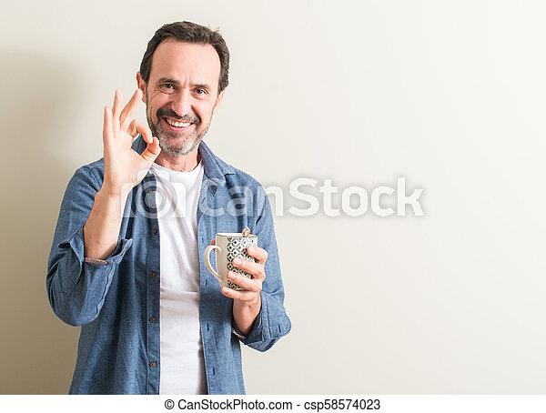 Señor bebiendo café en una taza haciendo bien signo con dedos, excelente símbolo - csp58574023