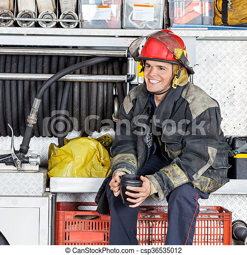 Bombero feliz sosteniendo taza de café en el camión en la estación de bomberos - csp36535012